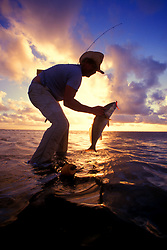 Stock photo of a man pulling a freshly caught fish from the Gulf of Mexico at sunset