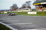 """Blurry photo of British Sports racing driver Bill de Selincourt (1921-2014) driving Lister-Jaguar """" Knobbly"""" car, BARC event Goodwood, March 1961"""