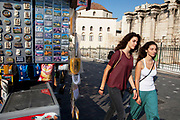 Women walking past a stall selling postcards and souvenirs to tourists in the area of Monastiraki very near to the Acropolis. This area is the centre of tourism in the capital with shopping areas, restaurants, the flea market and the historical ancient temples all nearby. Athens is the capital and largest city of Greece. It dominates the Attica periphery and is one of the world's oldest cities, as its recorded history spans around 3,400 years. Classical Athens was a powerful city-state. A centre for the arts, learning and philosophy.