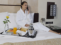 beautiful calm and serene woman in palace hotel room having her breakfast phoning