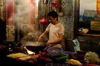 A young man thoroughly enjoying cooking food to order in a Shenzhen market.