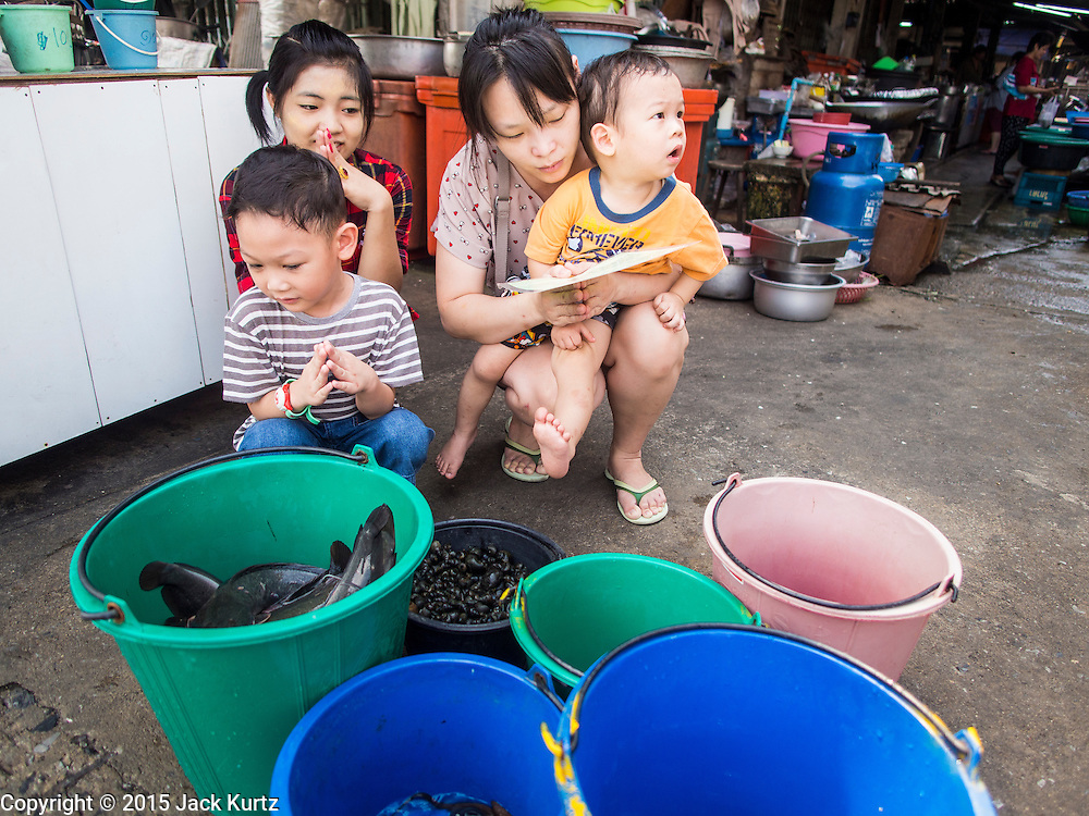20 APRIL 2015 - BANGKOK, THAILAND:   A Buddhist family prays before releasing fish into Khlong Bangkok Yai in the Thonburi section of Bangkok. Releasing animals, frequently small birds buy also fish and reptiles, is a common way of making merit in Buddhist countries.   PHOTO BY JACK KURTZ