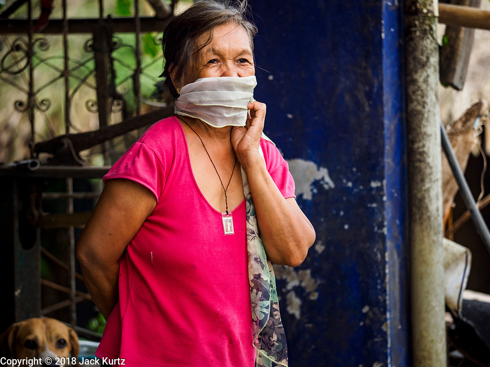 """22 JANUARY 2018 - GUINOBATAN, ALBAY, PHILIPPINES: A woman in Guinobatan wears a face mask because of an ash fall caused by the eruption of Mayon volcano. Several communities in Guinobatan were hit ash falls from the eruptions of the Mayon volcano and many people wore face masks to protect themselves from the ash. There were a series of eruptions on the Mayon volcano near Legazpi Monday. The eruptions started Sunday night and continued through the day. At about midday the volcano sent a plume of ash and smoke towering over Camalig, the largest municipality near the volcano. The Philippine Institute of Volcanology and Seismology (PHIVOLCS) extended the six kilometer danger zone to eight kilometers and raised the alert level from three to four. This is the first time the alert level has been at four since 2009. A level four alert means a """"Hazardous Eruption is Imminent"""" and there is """"intense unrest"""" in the volcano. The Mayon volcano is the most active volcano in the Philippines. Sunday and Monday's eruptions caused ash falls in several communities but there were no known injuries.    PHOTO BY JACK KURTZ"""
