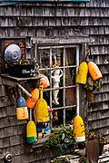 Buoys decorate the side of a fish shack on a foggy morning in the quaint fishing harbor of Port Clyde, Maine.