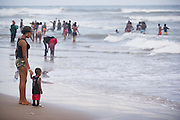 A woman holds the hand of a child as he watches the waves at Labadi Beach in Accra, Ghana on Sunday October 8, 2007. Also known as La Pleasure Beach, it is one of the city's most popular hangouts, especially on Sunday afternoons.