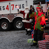 WALNUTPORT, PA:  The Sheats family greets cars at Becky's Drive-In Movie Theater, as the Lehigh Township Fire Company held a physically distanced greet Santa Claus drive through event in Walnutport, PA on December 5, 2020.  The pandemic has forced difficult decisions about maintaining the holiday tradition of visits to Santa Claus versus safety concerns.  Plexiglass dividers, face shields, and physical distancing are among the precautions for those locations that have proceeded with Santa photo opportunities.  CREDIT:  Mark Makela for The New York Times