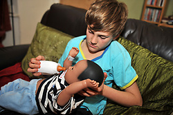 Boy minds his sister's 'real care baby' as part of a school project to prevent teenage pregnancy.  The baby needs real care and is monitored by computer to check the progress and to make the situation realistic. MR