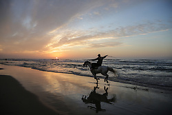 January 3, 2018 - Gaza, Gaza Strip - Palestinian rides a horse in the wet sand during sunset at the sea, off the coast of Gaza Strip. (Credit Image: © Nidal Alwaheidi/Pacific Press via ZUMA Wire)