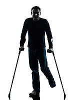 one man injured man with crutches in silhouette studio on white background