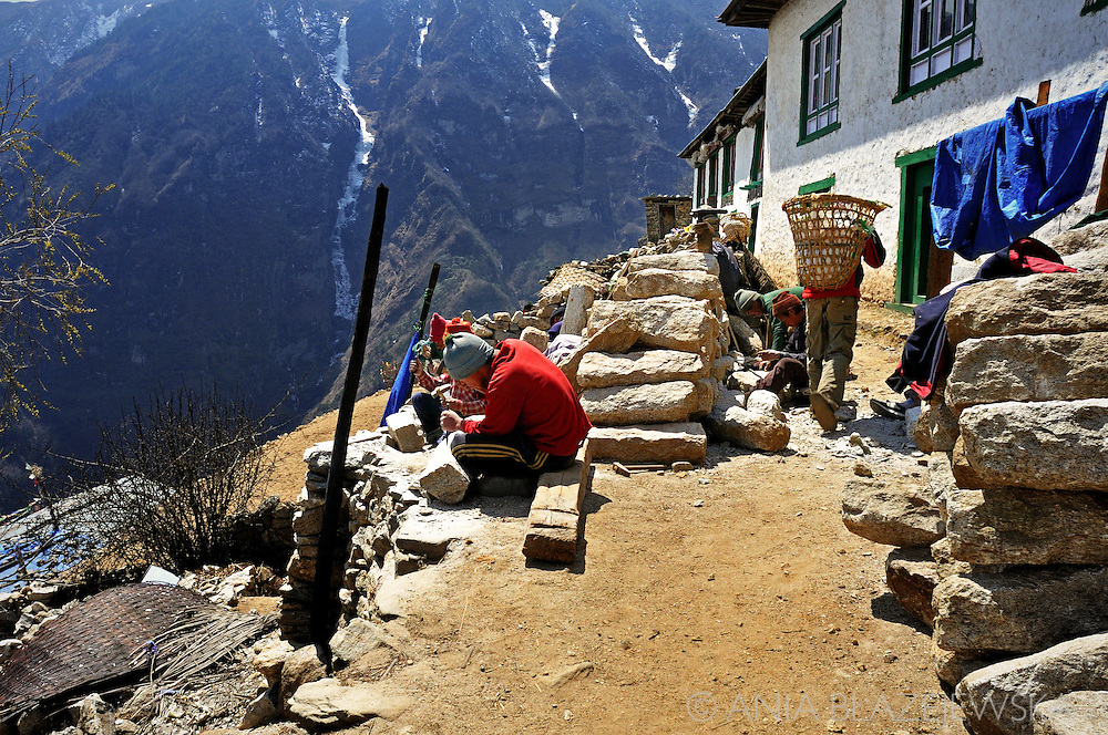 Nepal, Namche Bazaar. Man working with stones.