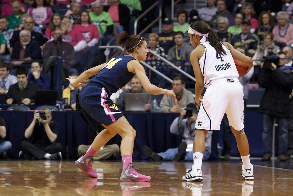 Notre Dame guard Skylar Diggins (#4) dribbles the ball as West Virginia forward Jess Harlee (#14) defends in first half action of NCAA Women's basketball game between West Virginia and Notre Dame.  The West Virginia Mountaineers upset the Notre Dame Fighting Irish 65-63 in game at Purcell Pavilion at the Joyce Center in South Bend, Indiana.