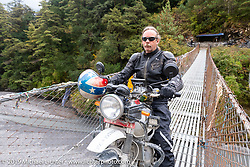 Round the World Doug Wothke riding across a suspension bridge on Motorcycle Sherpa's Ride to the Heavens motorcycle adventure in the Himalayas of Nepal. On the fourth day of riding, we went from Kalopani to Muktinath. Thursday, November 7, 2019. Photography ©2019 Michael Lichter.