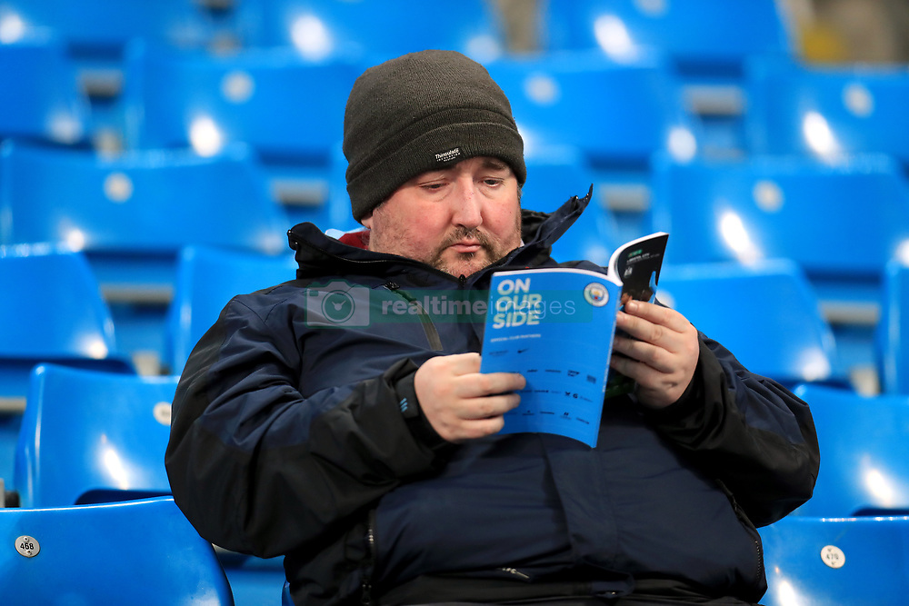 A fan in the stands reading the programme before the match starts