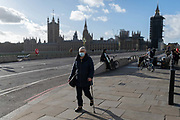 With the Houses of Parliament in the distance, a woman wearing a face covering walks over Westminster Bridge, on 12th November 2020, in London, England.