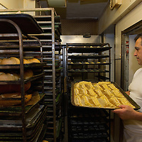 VENICE, ITALY - NOVEMBER 15:  A baker holds a tray of Impade, an almond biscuit, at theJewsh bakery at the Ghetto on November 15, 2011 in Venice, Italy. Established in 1516 the Ghetto of Venice was the area were Jews were compelled to live during the Venetian Republic. The English term 'ghetto' is derived from the Venetian term for 'slag' and refers to the refuse left the foundry that was located on the same island. In present times the ghetto is a multi-ethnical area area seen as the cultural heart of the city, but with five synagogues remains the centre of the of Jewish community.