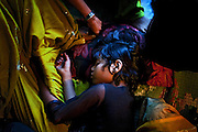Poonam, 10, feeling unwell in the middle of the afternoon, is sleeping next to her mother, Sangita Jatev, 39, inside their newly built home in Oriya Basti, one of the water-contaminated colonies in Bhopal, central India, near the abandoned Union Carbide (now DOW Chemical) industrial complex, site of the infamous '1984 Gas Disaster'.