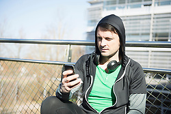 Man in sportswear with headphones and smart phone relaxing on bridge after workout