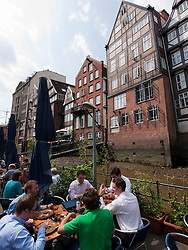 Small restaurant in front of historic half-timbered houses at Nikolaifleet in Hamburg Germany