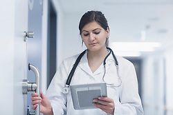 Young female doctor using a digital tablet in hospital corridor, Freiburg im Breisgau, Baden-Wuerttemberg, Germany