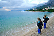 Two children (9 years old, 5 years old) on beach at sunset. Makarska, Croatia