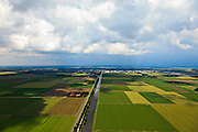 Nederland, Noordoostpolder, 30-06-2011; Urkerweg (Emmeloord aan de horizon). De Noordoostpolder (NOP), is een voorbeeld van moderne grootschalige polder met rationele verkaveling. De aanleg van de polder maakte  deel uit van de Zuiderzeewerken (plan Lely) en viel in 1942 droog. De meeste boerderijen (en dorpen) zijn van na de tweede wereldoorlog..The northeast polder (NOP), is an example of modern large-scale polder with rational allotment. The construction of the polder was part of the Zuiderzee Works (Lely plan), in 1942 the polder was dry. Most of the building, farmhouses and villages, is post-war..luchtfoto (toeslag), aerial photo (additional fee required).copyright foto/photo Siebe Swart