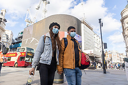 Licensed to London News Pictures. 24/10/2021. London, UK. Sunday shoppers wear masks on Piccadilly, London today as Health Secretary Sajid Javid orders the NHS to allow the over 50s to book their 3rd vaccine a month early to speed up the booster vaccination program. This week, Downing Street predicted new infections could rise to 100,000 a day this winter and urged eligible members of the public to get their booster jabs as soon as possible. Photo credit: Alex Lentati/LNP