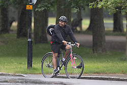 © Licensed to London News Pictures. 08/08/2021. London, UK. A man cycles during rain in Greenwich Park in South East London. A yellow weather warning for thunderstorms is in place for parts of England. Photo credit: George Cracknell Wright/LNP