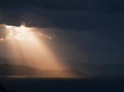 Sunlight streams through a break in storm clouds over the Bay f Biscay, near San Sebastian, Spain