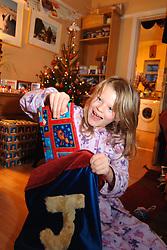Girl opening her stocking on Christmas Day morning UK