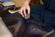 Printer Yoshio Kyoso applies ink to a woodblock as he works on a reproduction of Katsushika Hokusai's Fine Wind, Clear Morning. Adachi Foundation for the Preservation of Woodcut Printing, Tokyo, Japan, July 15, 2014. The Foundation works to preserve the original techniques of Japanese woodblock printing. As well as recreating classic ukiyo-e from the Edo period, they train and employ young artisans, and also educate about the art form.