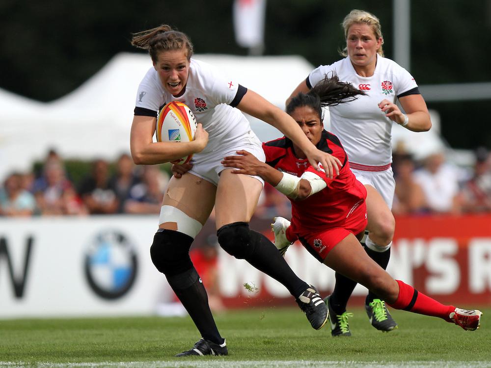 Emily Scarratt tackled by Magali Harvey. England v Canada Pool A match at WRWC 2014 at Centre National de Rugby, Marcoussis, France, on 9th August 2014
