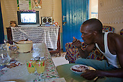 Kibet Serem having a lunch of pinto beans and rice here with his mother and sister-in-law. He cares for a small tea plantation that his father planted on their property near Kericho, Kenya when Kibet was a young boy and he is responsible for milking the cows that his family owns.  (Kibet Serem is featured in the book What I Eat: Around the World in 80 Diets. He is 25 years of age.) He sells extra milk to a nearby school for a government feeding program and gives some to his mother who makes yogurt and sells it. His staple food is ugali, a maize meal porridge.