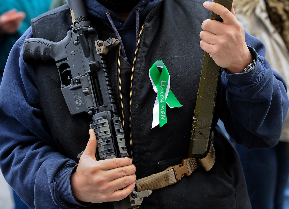 """A man who refused to be identified holds an AR-15 semi-automatic riffle at rally in support for gun rights at the Capitol in Hartford, Conn., Saturday, Jan. 19, 2013.  The rally, dubbed, """"Guns Across America"""", at Connecticut's state Capitol and state capitol buildings across the country   to raise concerns about possible new gun legislation that could affect gun owners' rights in the wake of the Dec. 14 school shooting at Sandy Hook Elementary School in Newtown. (AP Photo/Jessica Hill)"""