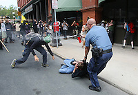 A police officer uses mace to repel another demonstrator attempting to rescue his comrade held by the officer during a protest march before the start of the Republican National Convention in St. Paul, Minnesota.