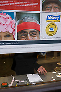 The hands and fingers of an anonymous customer is seen through a city Post Office window, behind a pension savings ad. Three faces of models used for this ad campaign by the Post Office peer out on to the street, telling the public of ways to invest in their futures. A single hand appears below in the window, surrounded by a moist stamp pad, biro and the remnants of various postal litter.