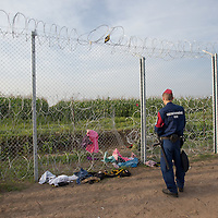 Police officer stands guard at an opening cut on the razor wire fence on the border between Serbia and Hungary near Roszke (about 174 km South of capital city Budapest), Hungary on September 15, 2015. ATTILA VOLGYI