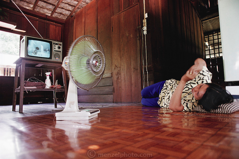 Buaphet Khuenkaew, 35, avoids working during the heat of the afternoon and dozes on the teak floor in front of the television that is showing one of her favorite Thai soap operas. The Khuenkaew family lives in a wooden 728-square-foot house on stilts, surrounded by rice fields in the Ban Muang Wa village, outside the northern town of Chiang Mai, in Thailand. Material World Project.