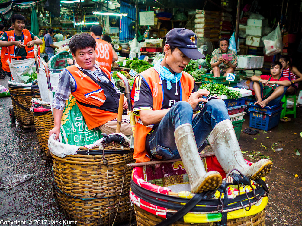 08 JUNE 2017 - BANGKOK, THAILAND: Porters wait for customers in Khlong Toey Market, Bangkok's main fresh market. Thai consumer confidence dropped for the first time in six months in May following a pair of bombings in Bangkok, low commodity prices paid to farmers and a sharp rise in the value of the Thai Baht versus the US Dollar and the EU Euro. The Baht is surging because of political uncertainty, related to Donald Trump, in the US and Europe. The Baht's rise is being blamed for a drop in Thai exports. This week the Baht has been trading at around 33.90 Baht to $1US, it's highest point in two years.      PHOTO BY JACK KURTZ