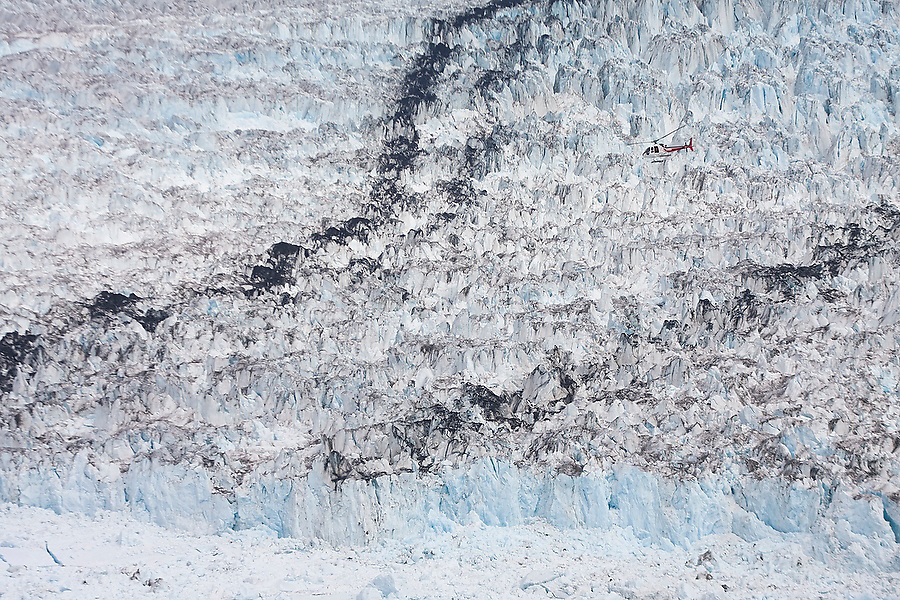A helicopter, carrying the Extreme Ice Survey crew, flies over the crevasses, moraines and seracs at the terminus of the Columbia Glacier, near Valdez, Alaska.