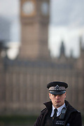 Police officer stands guard opposite the Houses of Parliament, after our people were killed including the attacker and 20 injured during a terrorist attack on Westminster Bridge and outside the Houses of Parliament, on 22nd March 2017, in central London, England. Parliament was in session and all MPs and staff and visitors were in lock-down while outside, the public and traffic were kept away from the area of Westminster Bridge and parliament Square, the scenes of the attack. It is believed a lone man crashed his car into pedestrians then, armed with a knife tried to enter Parliament, stabbing and killing a police officer at parliaments main gates.