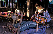 Farming villager A Hua, weaving a cloth on a traditional loom, Zha Lu Village, Yunnan Province, China.