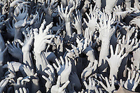 """The approach to Wat Rong Khun has a pond filled with spooky samsara to show human failures at enlightenment.This is depicted with grasping outstretched hands, grotesque """"gargolyles"""" to symbolize how people suffer from their bad karma."""