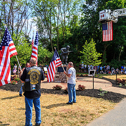 Ephrata, PA, USA - May 25, 2015: Community members hold American flags during the dedication ceremony of WWII Band of Brothers Commander Major Richard Winters Memorial.