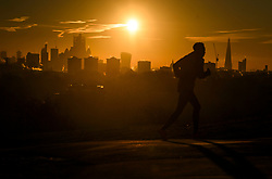 © Licensed to London News Pictures. 03/02/2019. London, UK. A man jogging through Primrose Hill in North London as the sun rises from behind the City of London on a cold winter morning. Large parts of the UK continue to be deluged with snow and freezing temperatures. Photo credit: Ben Cawthra/LNP