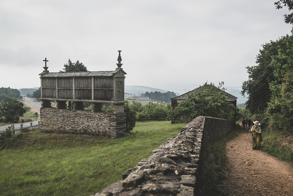 On the Camino de Santiago, between the towns of Portomarin and Palas de Rey, a pilgrim turns her head to view a traditional granary, called a hórreo. The pilgrim is Mara, from Germany, and she is walking the Camino in medieval clothing. (July 8, 2018)<br /> <br /> DAY 42: PORTOMARIN TO PALAS DE REI -- 24 KM