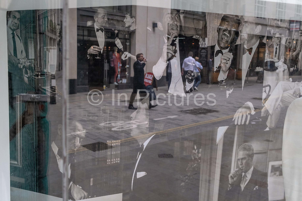 Merging with party images of the Rat Pack in the window of a menswear outfitters, are the reflection of a City worker taking a drink during the summer heatwave in Lime Street in the City of London, the capitals financial district, on 6th August 2020, in London, England.