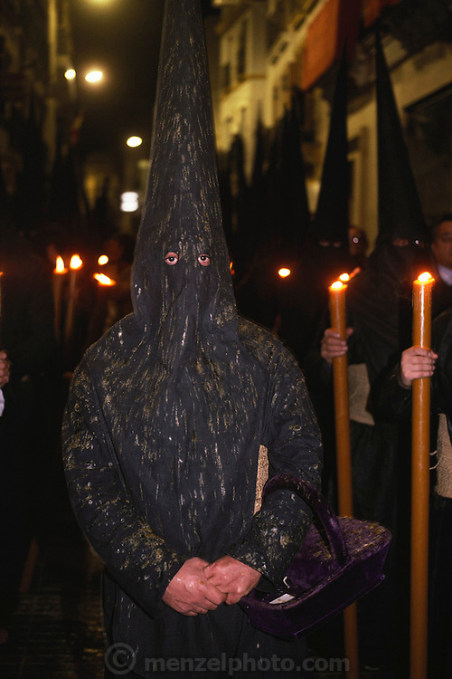 A hooded penitent in a night-time procession during Holy week in Seville, Spain. Street processions are organized in most Spanish towns each evening, from Palm Sunday to Easter Sunday. People carry statues of saints on floats or wooden platforms, and an atmosphere of mourning can seem quite oppressive to onlookers.