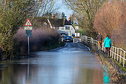 © Licensed to London News Pictures. 22/12/2019. Aylesbury, UK. People walk past a flooded area of road on Mill Lane in the village of Shabbington, parts of the road were submerged after the River Thame burst its banks during heavy rain across Buckinghamshire. Photo credit: Peter Manning/LNP