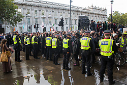 London, UK. 8 October, 2019. Police officers form a cordon in front of climate activists from Extinction Rebellion blocking Whitehall on the second day of International Rebellion protests to demand a government declaration of a climate and ecological emergency, a commitment to halting biodiversity loss and net zero carbon emissions by 2025 and for the government to create and be led by the decisions of a Citizens' Assembly on climate and ecological justice.