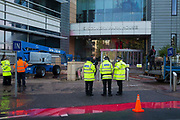 Kent Police officers monitor two Palestine Action activists occupying an area above the entrance to Discovery Park House as a team of workmen wash off red paint previously sprayed at the building by activists in protest against the presence in Discovery Park of an Instro Precision factory on 4th October 2021 in Sandwich, United Kingdom. Instro Precision is a subsidiary of Israels largest publicly-traded arms company Elbit Systems supplying high precision military equipment and Palestine Action contends that Instro Precision equipment has been used by the Israeli military against the population of Gaza.